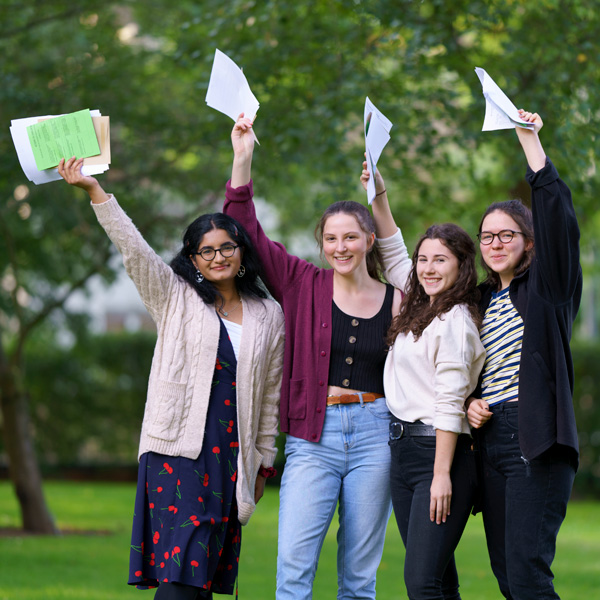 Four GCSE students hold up their results, smiling, against a backdrop of trees