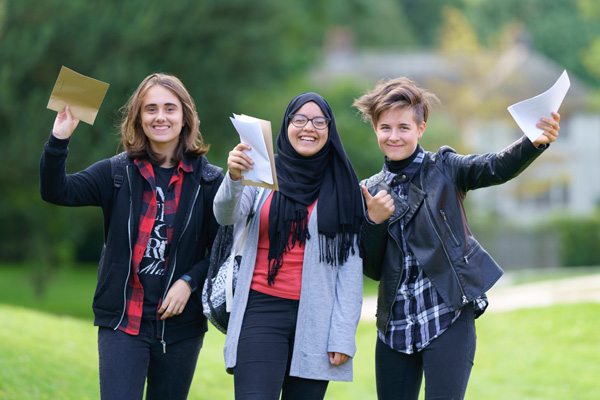 Three GCSE students hold up their results, smiling, against a backdrop of trees